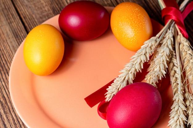 Красочные пасхальные яйца на коралловой тарелке с колосьями, на коричневом