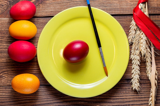 Красочные яйца на пасху на желтой табличке, кисть, колосья