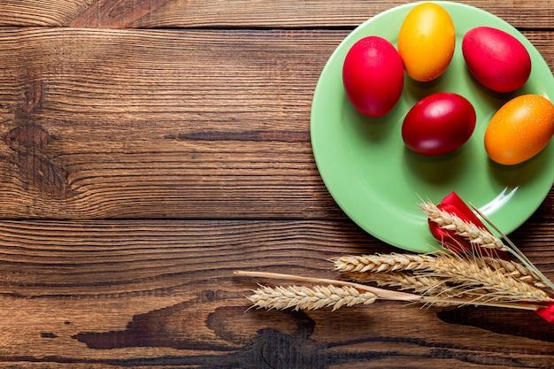 Красочные пасхальные яйца зеленые уши зерна плиты, на коричневой деревянной предпосылке с космосом экземпляра.