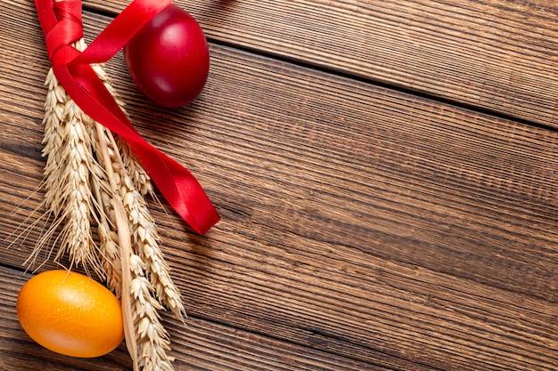 Красочные пасхальные яйца, колосья на коричневый деревянный фон с копией пространства