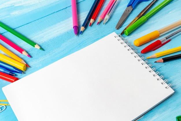 ペン、鉛筆、コピースペース付きのマーカーで空白のページ。学校のコンセプトに戻る