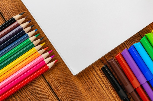 カラフルな鉛筆、マーカー、ペンとコピースペースを持つノートブックの空白のページ。学校のコンセプトに戻る