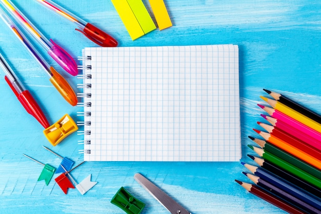 鉛筆、マーカー、コピースペースを持つ空白のノートブックページ。学校のコンセプトに戻る