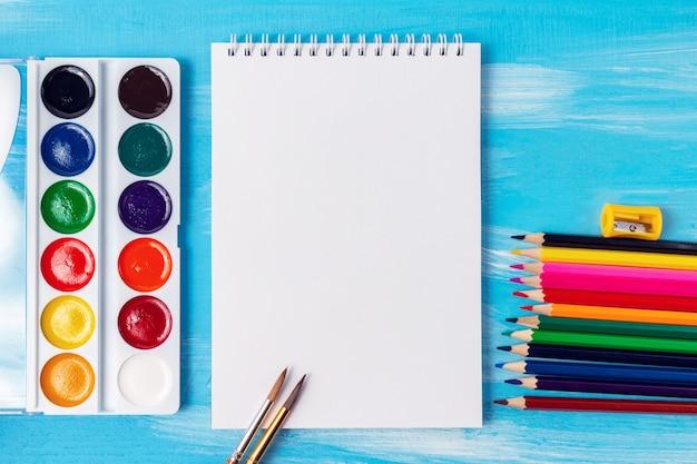 水彩、鉛筆、ブラシ、マーカー、コピー領域の空白のノートブックページ。事務用品と学校のコンセプトに戻る。