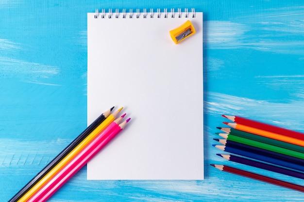 鉛筆、マーカー、コピースペースを持つ空白のノートブックページ。事務用品と学校のコンセプトに戻る。