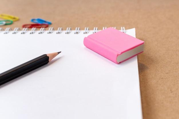 ノート空白ページ鉛筆と消しゴムで構成。学校のコンセプトに戻る