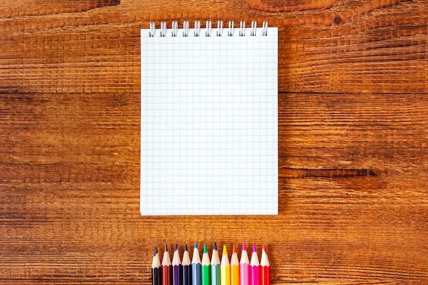 コピースペースを持つノートブック空白ページカラフルな鉛筆。学校のコンセプトに戻る