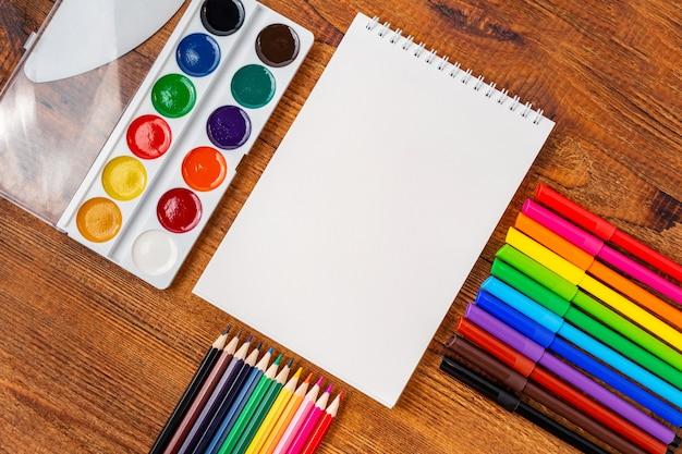 カラフルな鉛筆、マーカー、コピースペースと水彩画のノートブックの空白のページ。