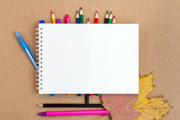 ノート空白ページカラフルな鉛筆、マーカー、水彩画、コピースペースと紅葉のコンポジション。学校のコンセプトに戻る