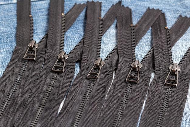 青い木製の背景に手作りの縫製仕立て革細工革細工のためのスライダーパターンで黒い金属真鍮ジッパーストライプの多くを詰める