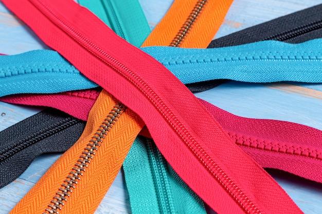 青い塗られた木製の背景に手作りの縫製仕立てのスライダーパターンでカラフルなプラスチックと金属のジッパーストライプの多くをパックセレクティブフォーカスを閉じる