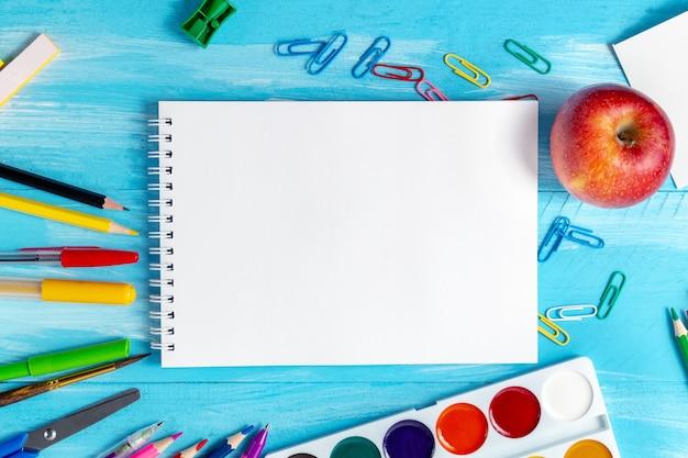 事務用品の空白のメモ帳シートは、ペン、鉛筆、ブラシ、フェルトペン、マーカー、ペーパークリップです。