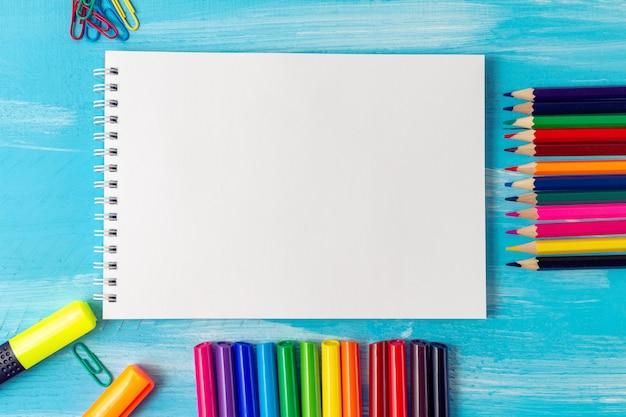 ペン、鉛筆、ブラシ、フェルトペン、マーカー、ペーパークリップ付きの空白のメモ帳シート。学校のコンセプトに戻る。
