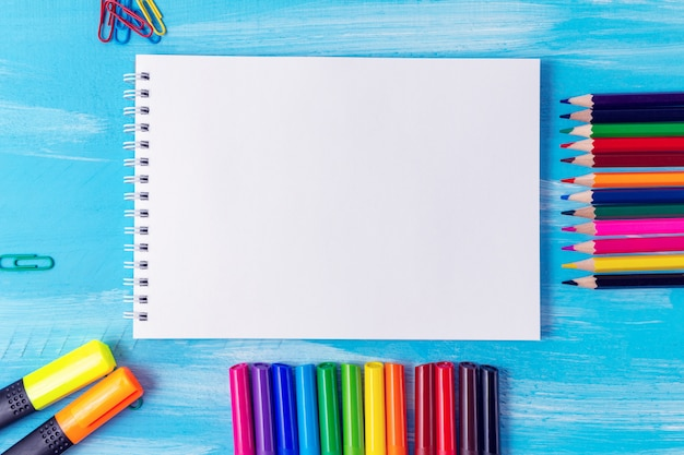 文房具のオフィスで空白のメモ帳シートは、ペン、鉛筆、ブラシ、フェルトペン、マーカー、ペーパークリップを提供します。学校のコンセプトに戻る