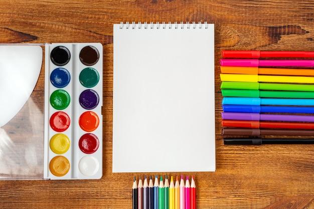 ノート空白ページカラフルな鉛筆、マーカー、ペンのモックアップで構成学校のコンセプトに戻る