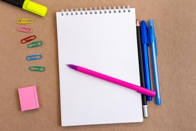 ノート空白ページカラフルな鉛筆、マーカー、コピースペース付きのペンで構成。学校のコンセプトに戻る