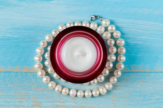 板張りの青い木製の真珠のネックレスと赤いガラスの瓶に美容クリーム