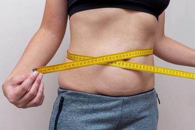 女性は黄色のテープで腰を測定します。ダイエットフィットネスの概念。