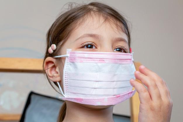 検疫隔離中に自宅で医療用防護マスクを身に着けている子供の女の子