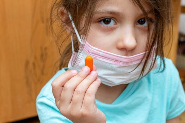 検疫隔離中に自宅で手に薬と一緒に医療用防護マスクを身に着けている子供の女の子