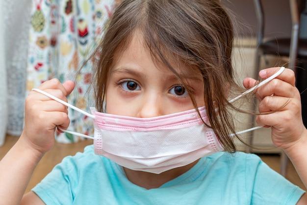 検疫隔離中に自宅で医療用防護マスクを着ている少女