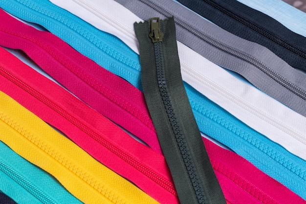 カラフルなプラスチックと金属のジッパーストライプパターンの多くをパック、背景をクローズアップ