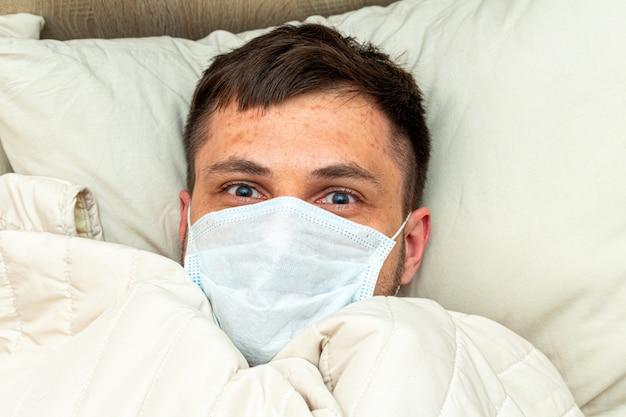 Испуганный мужчина в медицинской маске лежит в постели