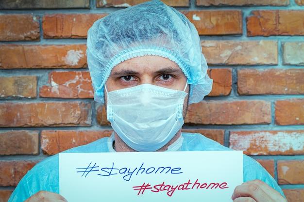 Мужчина в защитном костюме с надписью на листе остается дома
