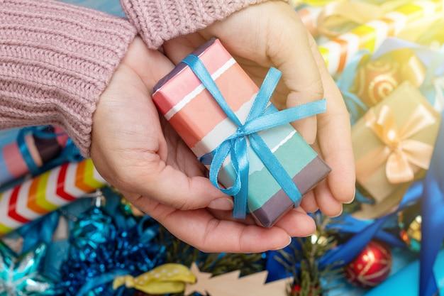 ギフトプレゼントボックスを保持しているニットセーターの手。クリスマス休暇の準備の概念。