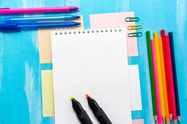Пустой лист блокнота с ручками, карандашами, кистями, маркерами, скрепками и копией пространства