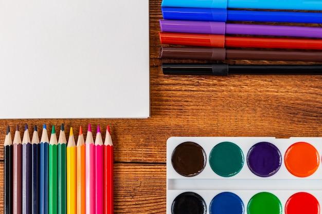 Композиция с ноутбука пустой страницы красочные карандаши, маркеры с копией пространства.