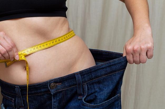 非常に大きなジーンズを保持しているスリムな女性。減量後の食事療法。