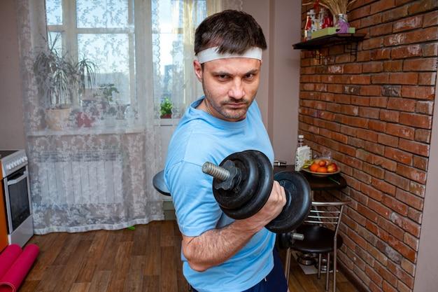 ダンベルを持って積極的な面白い感情的な男。隔離検疫中に自宅でトレーニング。