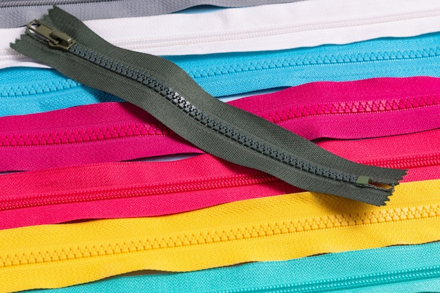 手作り縫製仕立てのためのカラフルなプラスチックジッパーストライプパターンの多く。