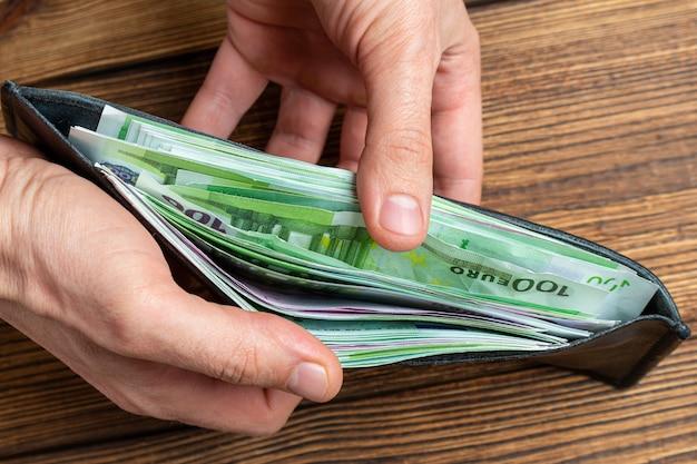 Руки держат кошелек полный денег банкнот