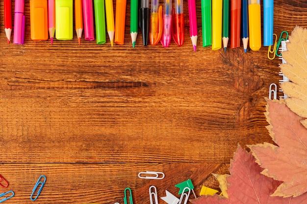 カラフルな鉛筆、マーカー、紅葉とペンで構成。学校のコンセプトに戻る