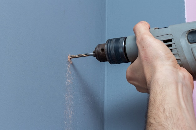 ドリルのクローズアップで灰色の壁を掘削
