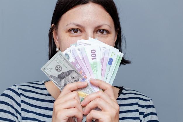 Женщина закрывает лицо банкнотами