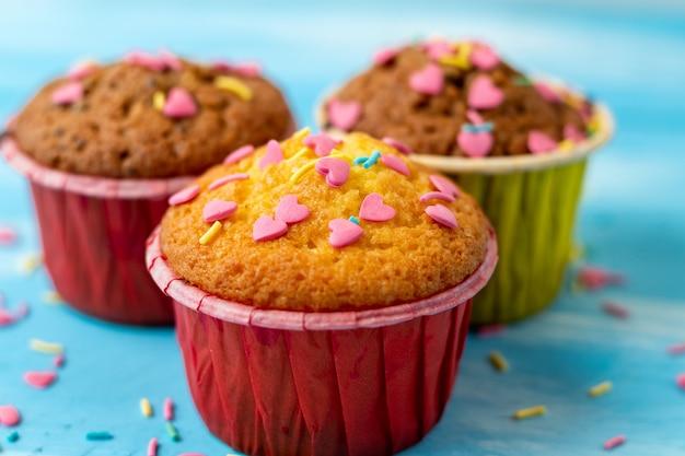 Вкусные домашние красочные кексы с кондитерской в форме сердца крупным планом