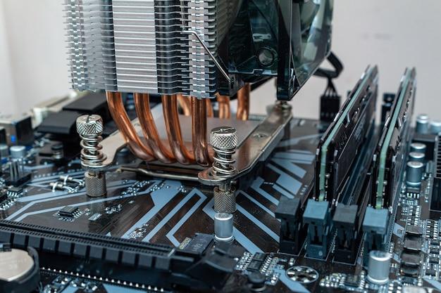 パーソナルコンピューターのプロセッサにクーラーを取り付ける。サービス内のコンピューターメンテナンスをアップグレードするプロセス。