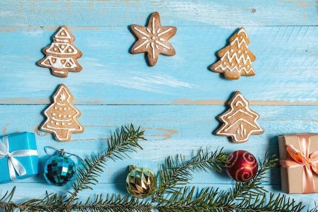 Подарки, пихта, еловые ветки, печенье на синем фоне деревянные крупным планом