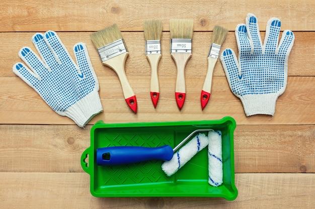 Композиция с инструментами для рисования, кистями, перчатками и валиком на деревянном столе