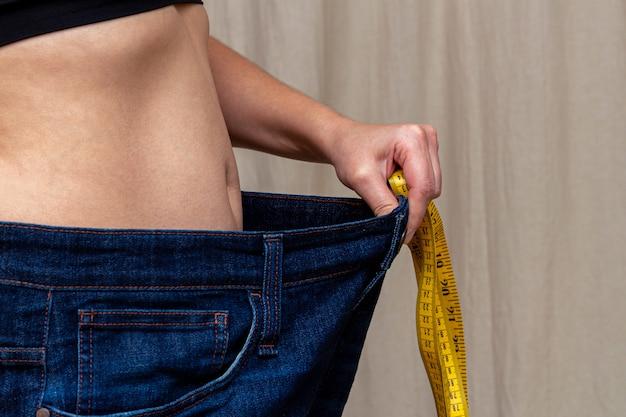 非常に大きなジーンズを保持しているスリムな女性。減量ダイエット後。