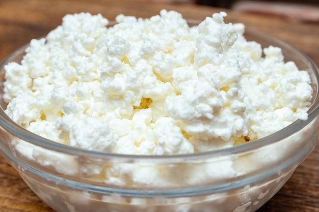 ファームカッテージチーズは木製の背景タンパク質健康ダイエットエコ製品にクローズアップ