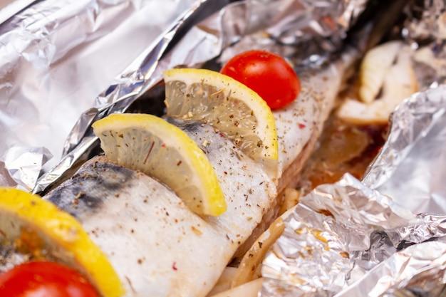 レモンとチェリートマトとスパイスの健康的なおいしいおいしい食べ物とホイルの生サバ