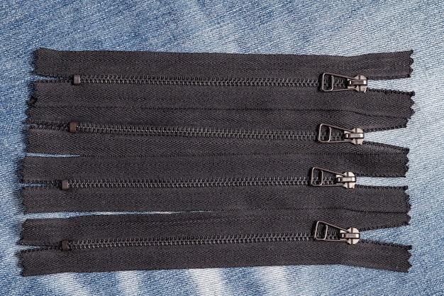 青いデニムの背景に手作りのスライダーパターンで黒い金属真鍮ジッパーストライプをたくさん詰める