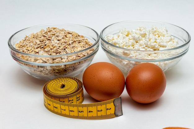 穀物、測定テープ、ファームコテージチーズ、卵は白い背景にクローズアップ。タンパク質健康ダイエット脂肪無料コンセプト。