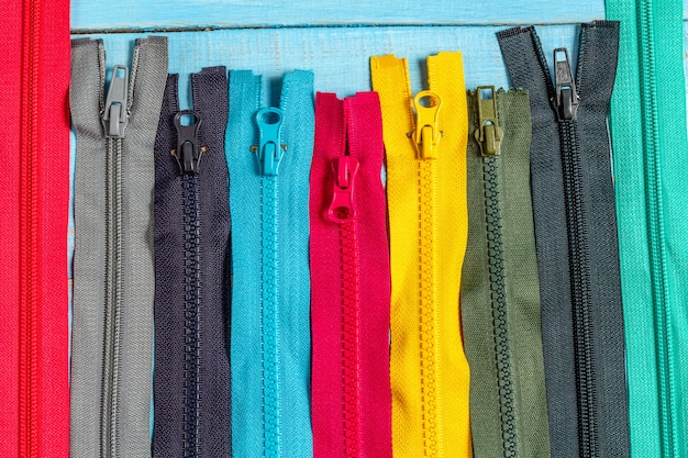 青いデニムの背景に手作りの縫製仕立てのセレクティブフォーカスをクローズアップのスライダーパターンでカラフルなプラスチックと金属ジッパーストライプの多くをパックします。