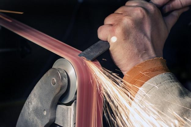Заточка лезвия на ленточной шлифовальной машине. нож, делая мастер руки крупным планом.