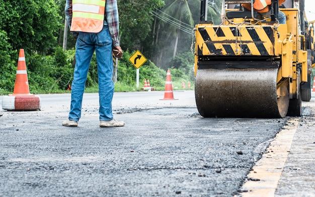 アスファルトの道路の修理を修理中に立っているエンジニアと小さなアスファルトローラーを背面します。道路建設、産業、チームワークの労働者。